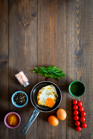 Recipe of fried eggs with vegetables. Ready eggs in a frying pan near cherry tomatoes, greenery, spices, raw eggs on dark wooden background top view.