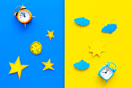 Sleep time, clock on the bed and time to awake concept. Alarm clock near sun, moon, stars cutout on blue and yellow background top view.