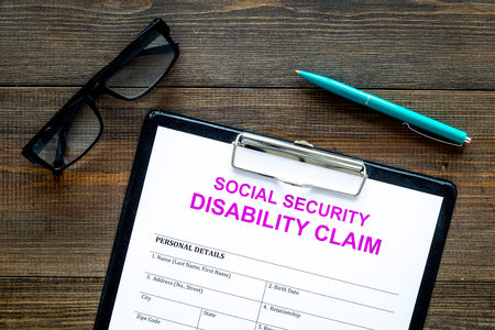 Social security. Disability claim form near glasses on dark wooden background top view