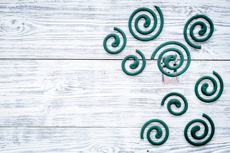 Mosquito repellent for outdoor: garden, summer house, picnic. Green spiral on grey wooden background top view copy space pattern