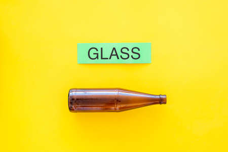 Waste suitable for recycle. Glass bottle near printed word glass on yellow background top view copy space