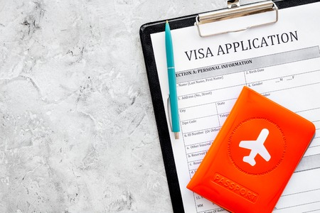 Visa processing, registration. Visa application form near passport cover with airplane on grey background top view.