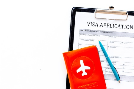 Visa processing, registration. Visa application form near passport cover with airplane on white background top view copy space Stock Photo