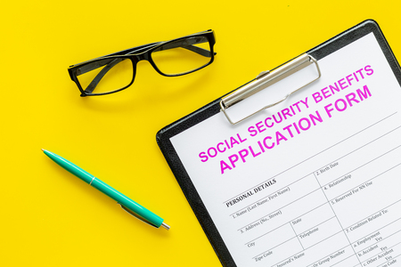 Social security benefits. Application form near pen and glasses on yellow background top view. Stock Photo