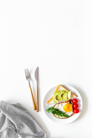 Healthy hearty breakfast. Fried eggs with vegetables near toast with avocado on white background top view copy space