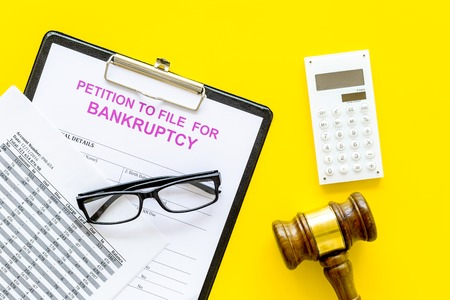 Petition to file for bankruptcy. Empty form ready to fill near calculator on yellow background top view. Standard-Bild - 108162694