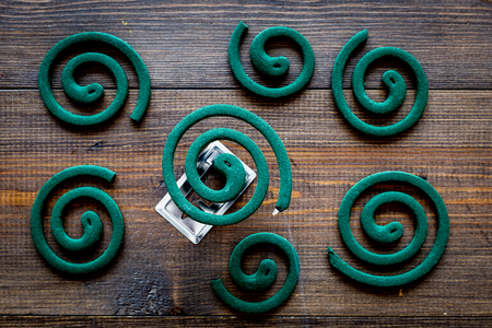 Mosquito repellent for outdoor: garden, summer house, picnic. Green spiral on dark wooden background top view pattern Archivio Fotografico - 108168633