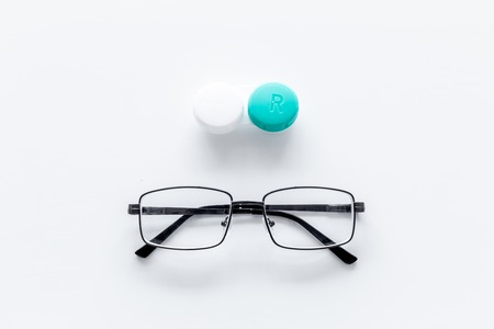 Products help see better. Glasses with transparent optical lenses and eye lenses on white background top view copy space closeup Stock Photo