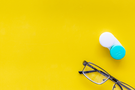Products help see better. Glasses with transparent optical lenses and eye lenses on yellow background top view space for text closeup Stock Photo - 108168652