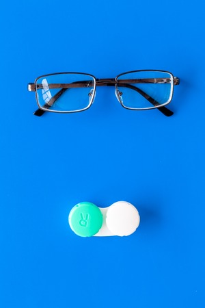Products help see better. Glasses with transparent optical lenses and eye lenses on blue background top view copy space closeup