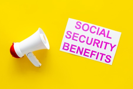 Printed words social security benefits near megaphone on yellow background with computer keyboard top view space for text