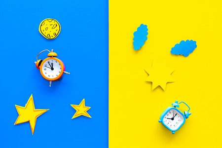 Sleep time, clock on the bed and time to awake concept. Alarm clock near sun, moon, stars cutout on blue and yellow background top view