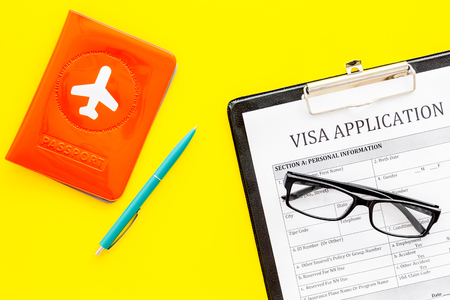 Visa processing, registration. Visa application form near passport cover with airplane on yellow background top view Stock Photo