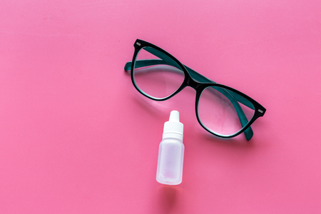 Eye health. Glasses with transparent optical lenses and eye drops on pink background top view.