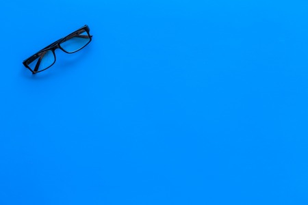 Glasses with transparent optical lenses on blue background top view.