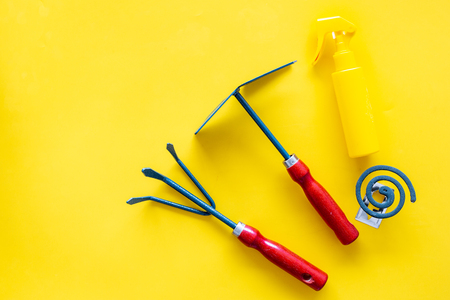 Mosquito protection for garden. Mosquito coil and spray near garden tools on yellow background top view.