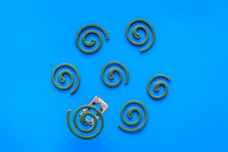 Mosquito repellent for outdoor : Garden, summer house, picnic. Green spiral on blue background top view.