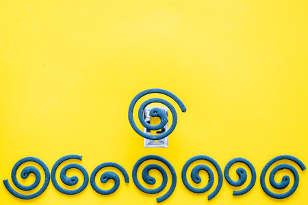 Mosquito repellent for outdoor : Garden, summer house, picnic. Green spiral on yellow background top view. Stock Photo