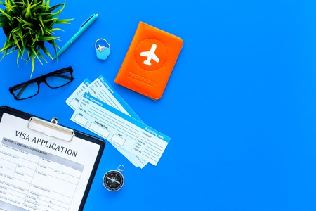 Preparing to travel. Legalize papers. Visa application form near passport and airplane ticket on blue background top view.