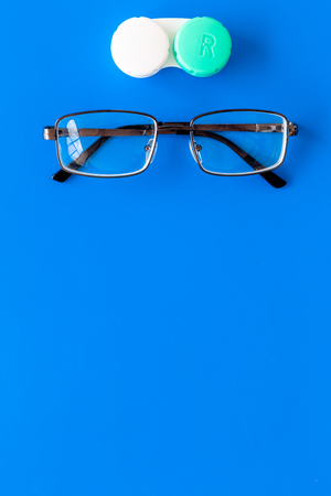 Products help see better. Glasses with transparent optical lenses and eye lenses on blue background top view. Stock Photo