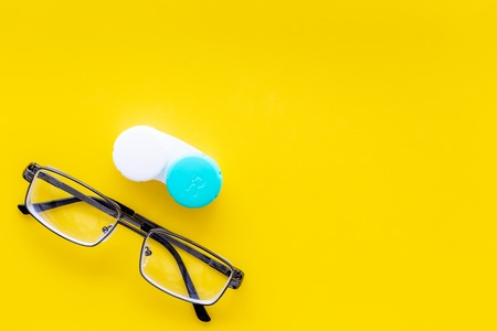 Products help see better. Glasses with transparent optical lenses and eye lenses on yellow background top view. Stock Photo - 108237678