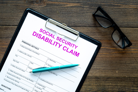 Social security. Disability claim form near glasses on dark wooden background top view.
