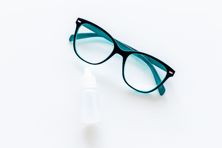 Eye health. Glasses with transparent optical lenses and eye drops on white background top view.