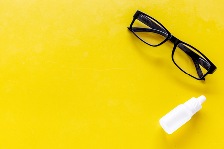 Eye health. Glasses with transparent optical lenses and eye drops on yellow background top view. Stock Photo - 108301540