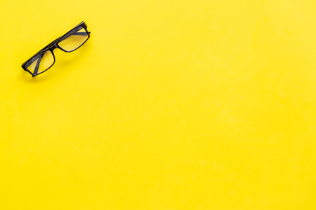 Glasses with transparent optical lenses on yellow background top view.