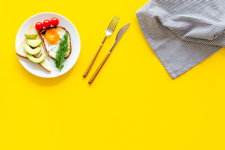 Healthy hearty breakfast. Fried eggs with vegetables near toast with avocado on yellow background top view.