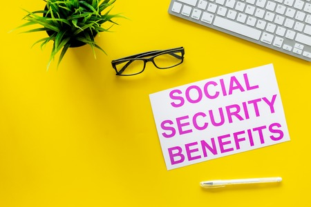 Printed words social security benefits on yellow office desk background with computer keyboard top view copy space