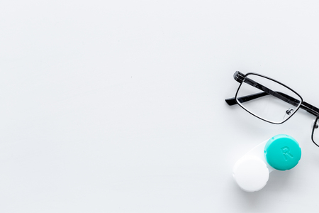 Products help see better. Glasses with transparent optical lenses and eye lenses on white background top view.