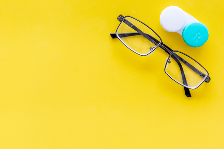 Products help see better. Glasses with transparent optical lenses and eye lenses on yellow background top view. Stock Photo