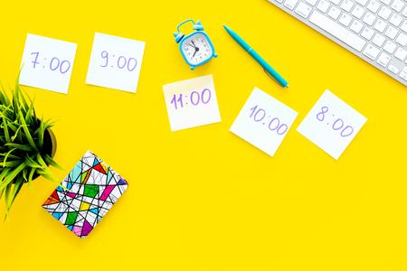Studenten plannen. Briefpapier met tijd van lessen op geel bureau met bovenaanzicht kopie ruimte van het computertoetsenbord