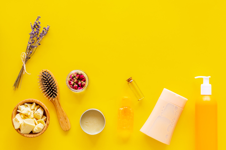 Professional shampoo, balm, conditioner based on jojoba, argan or coconut oil. Bottles and oil on yellow background top view copy space Stok Fotoğraf