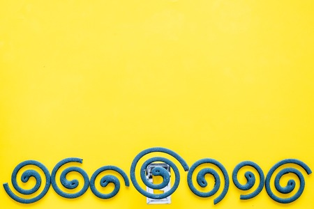 Mosquito repellent for outdoor: garden, summer house, picnic. Green spiral on yellow background top view copy space pattern