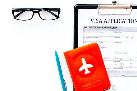 Visa processing, registration. Visa application form near passport cover with airplane on white background top view copy space Фото со стока