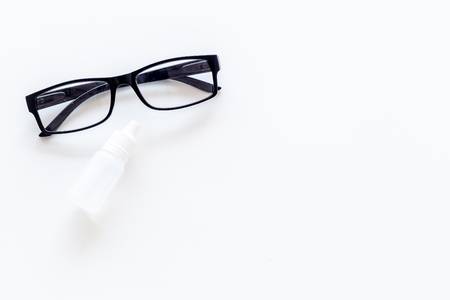 Eye health. Glasses with transparent optical lenses and eye drops on white background top view copy space closeup Stock Photo