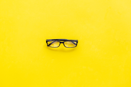 Glasses with transparent optical lenses on yellow background top view copy space