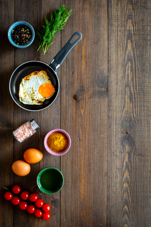 Recipe of fried eggs with vegetables. Ready eggs in a frying pan near cherry tomatoes, greenery, spices, raw eggs on dark wooden background top view copy space Banco de Imagens - 108384824