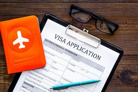 ビザ処理、登録。暗い木製の背景トップビューに飛行機でパスポートカバーの近くのビザ申請フォーム