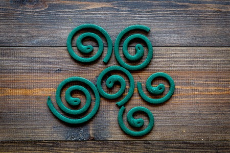 Mosquito repellent for outdoor: garden, summer house, picnic. Green spiral on dark wooden background top view copy space pattern Archivio Fotografico - 108420376