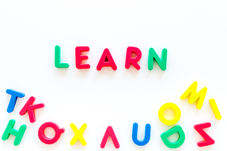 Children learn read concept. Word learn written by plastic letters on white background top view.