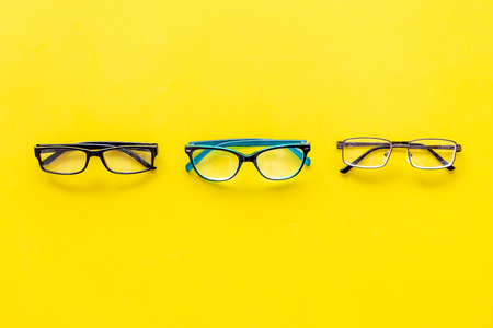 Glasses with transparent optical lenses on yellow background top view copy space Stock Photo - 108576043
