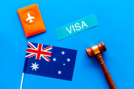 Visa to Australia concept. Text visa near passport cover and australian flag, hammer on blue background top view