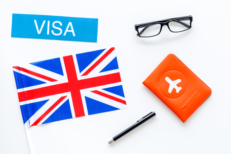 Immigration to Britain concept. Text immigration near passport cover and british flag on white background top view