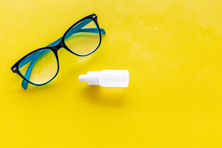 Eye health. Glasses with transparent optical lenses and eye drops on yellow background top view space for text closeup Stock Photo