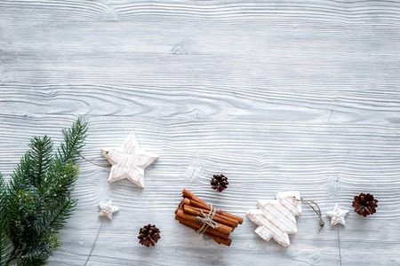 Spruce branch, cones and vintage toys in shape of spruce and stars on grey background for decoration on chrismas or new year top view copy space
