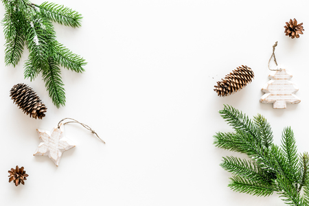 Spruce branch, cones and vintage toys in shape of spruce and stars on white background for decoration on chrismas or new year top view copy space Stock Photo