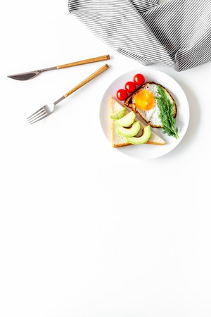 Healthy hearty breakfast. Fried eggs with vegetables near toast with avocado on white background top view.